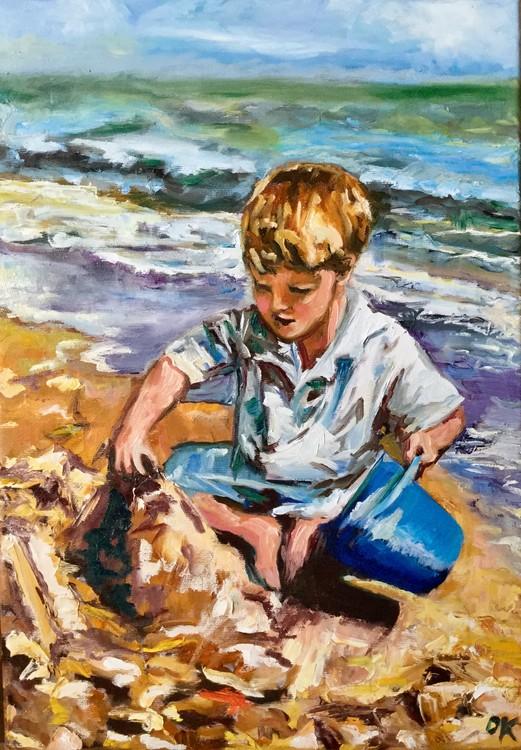 Boy is making a sand castle