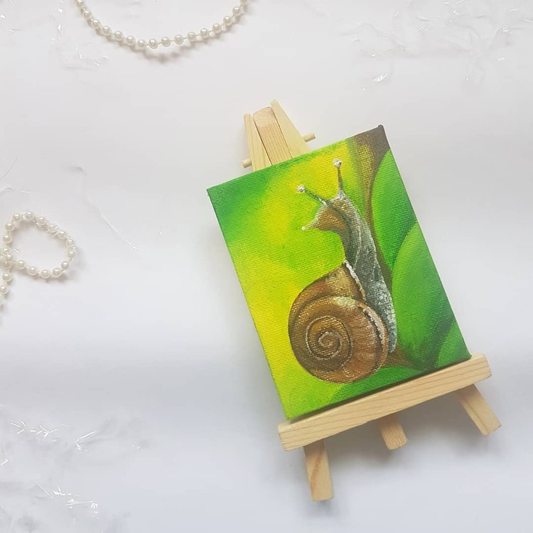curious snail in acrylics on mini canvas with mini easel
